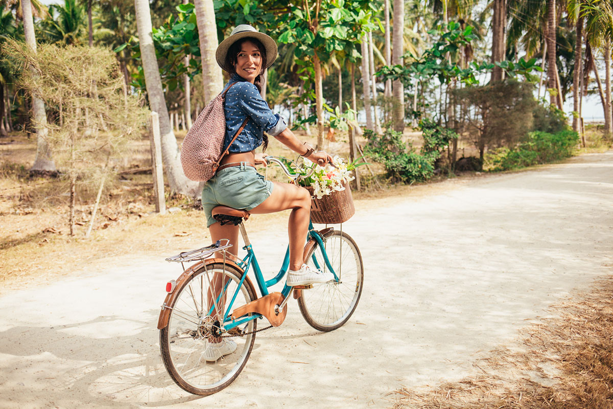 Happy Woman Riding a Bike in a Tropical Setting